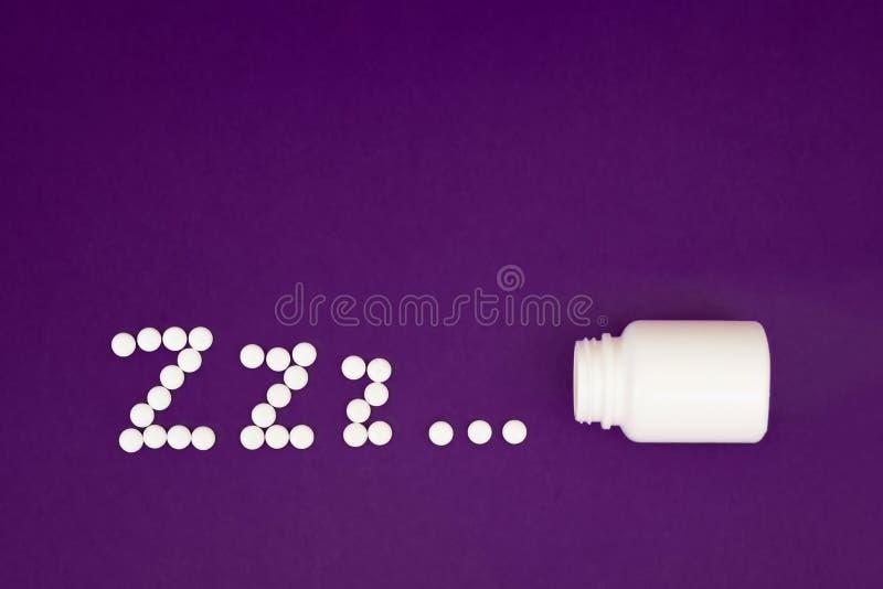 Le zzz d'inscription a fait à partir des pilules blanches débordant la bouteille de pilule sur le fond violet photo stock
