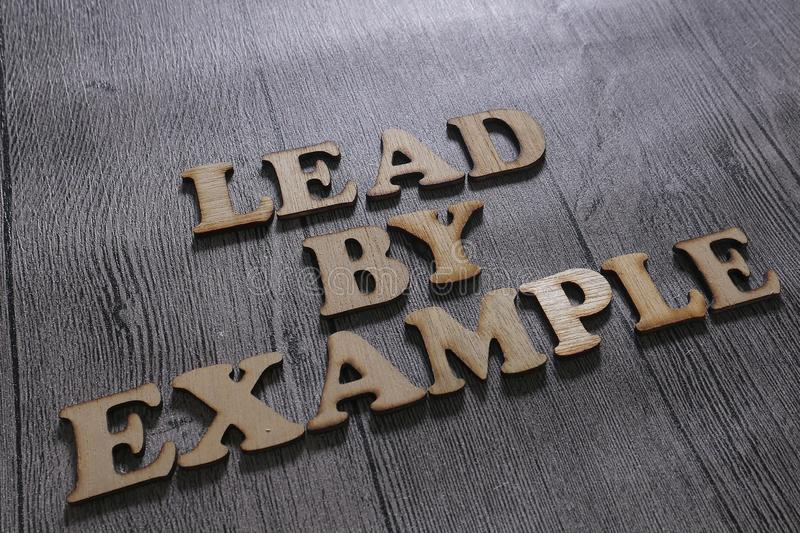 Lead By Example, Business Words Quotes Concept. Lead by Example, business motivational inspirational quotes, wooden words typography lettering concept stock photos