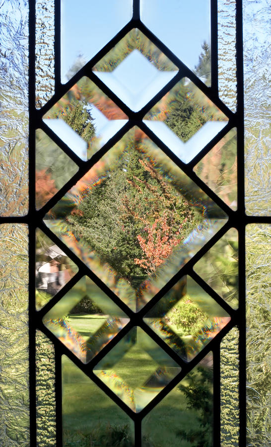 Lead paned window. Fall view through a lead-paned, frosted glass window royalty free stock photo
