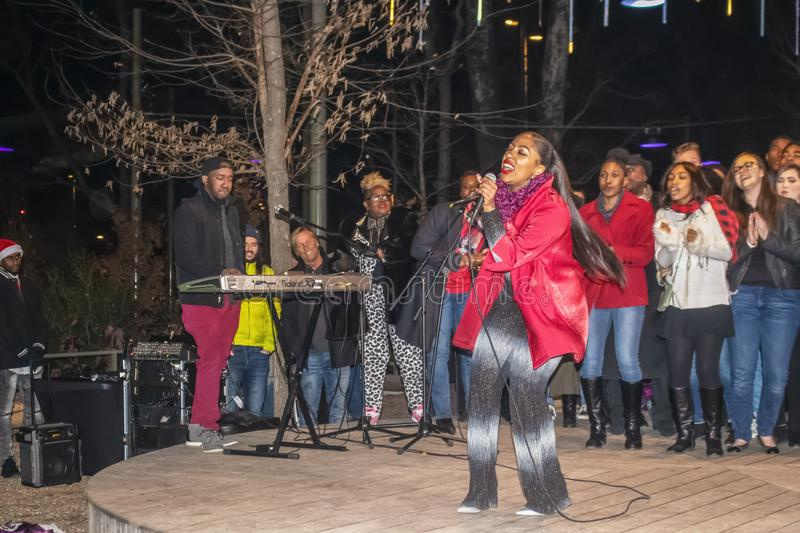 Lead singer of multi ethnic group rocking it on outdoor stage Christmas concert at Gathering Place public stock photography
