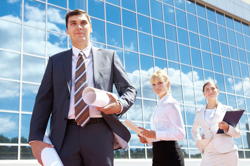 Leader. Portrait of successful leader holding rolled papers with two employees behind stock photos