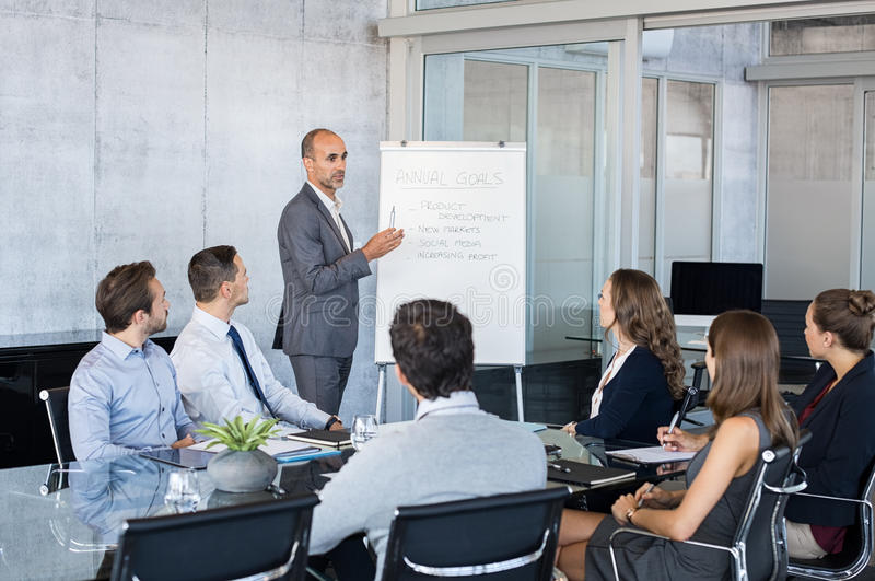 Leader briefing business people. Confident mature businessman giving a presentation to his team in modern office. Business brief with annual goals with employees stock image