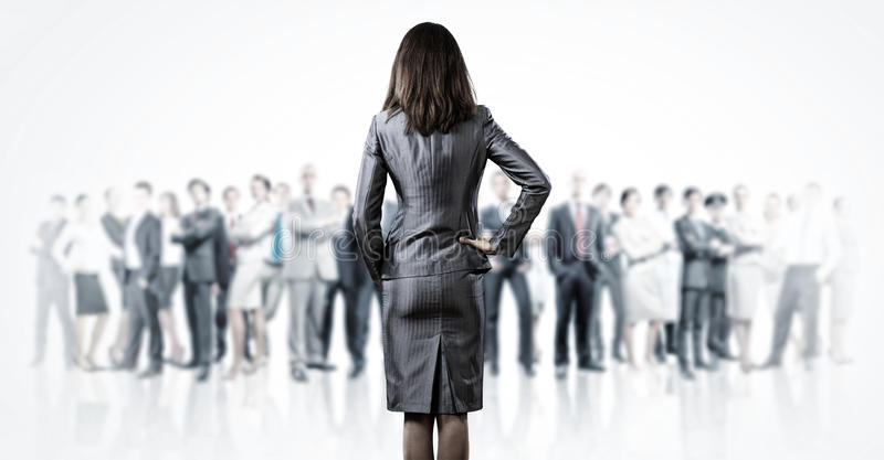Leader in business. Powerful businesswoman standing with back with business team at background royalty free stock image
