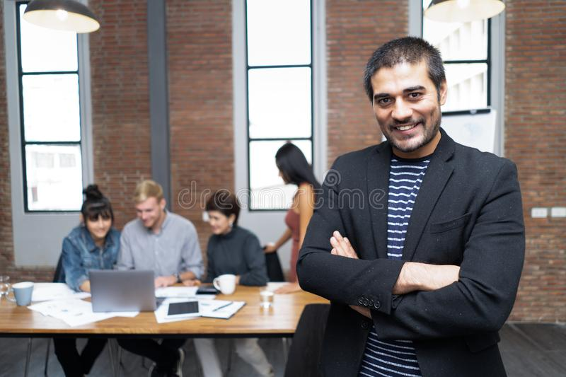 Leader businessman executive is standing with arms crossed looking at camera in front while colleague in background. royalty free stock image