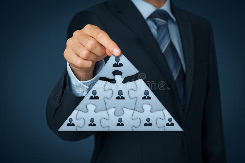Leader and CEO. CEO, leadership and corporate hierarchy concept - recruiter complete team represented by puzzle in pyramid scheme by one leader person (CEO royalty free stock image