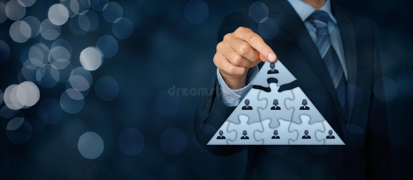 Leader and CEO. CEO, leadership and corporate hierarchy concept - recruiter complete team represented by puzzle in pyramid scheme by one leader person (CEO) royalty free stock images