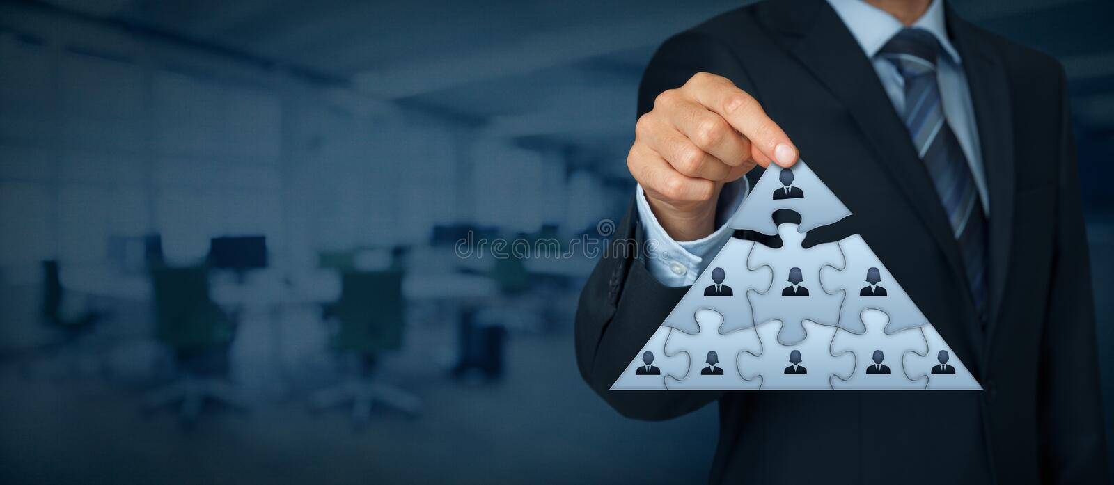 Leader and CEO. CEO, leadership and corporate hierarchy concept - recruiter complete team represented by puzzle in pyramid scheme by one leader person (CEO) royalty free stock image
