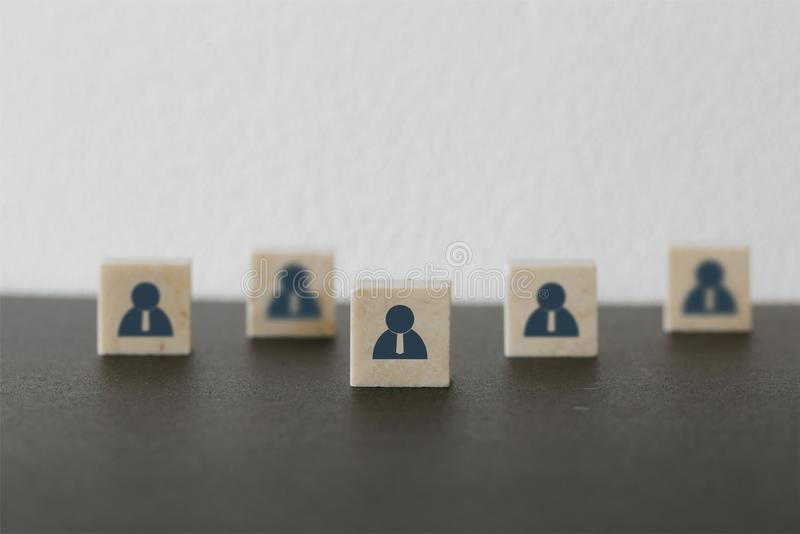 Leader with idea and innovation. Marble block with  icon people standing out from the crowd. Successful business team leader. Leader with idea and innovation stock image