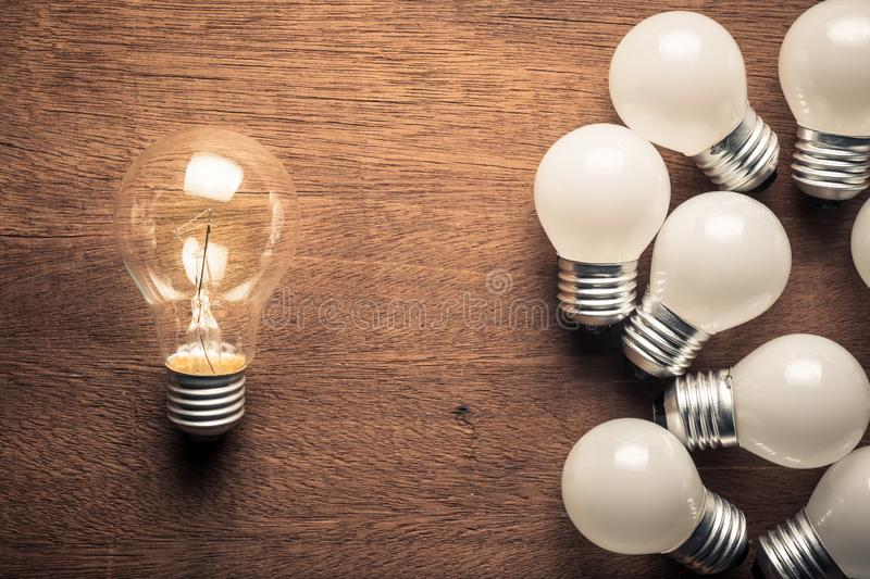 Leader Light Bulb. Bigger light bulb glowing out of the group of small light bulbs, success idea is simple but different royalty free stock photo