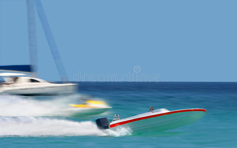 Leader. Racing of speedy boats. The man on the speedy boat with the red line is flying & leading the colorful racing competition. The background is blurred. The