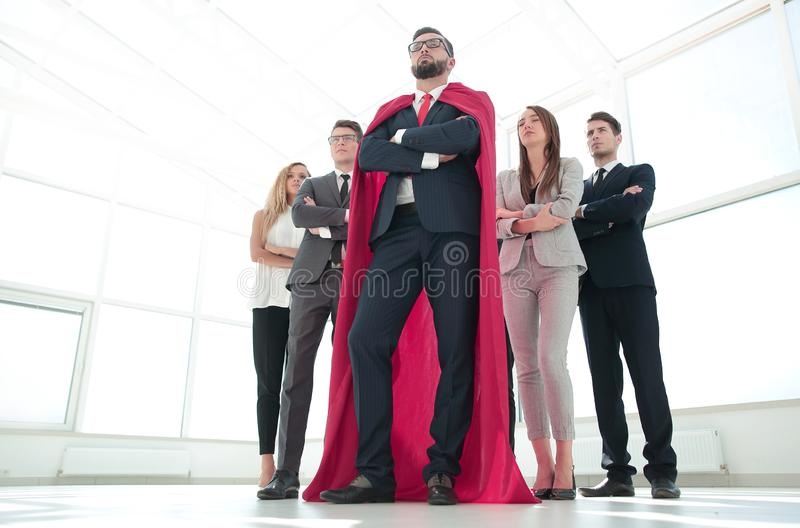 Leader in the red cloak and the business team standing together stock images
