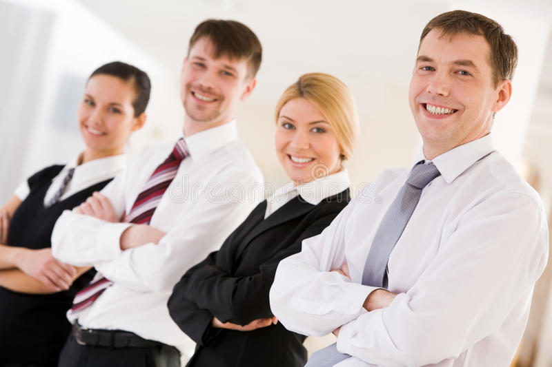 Leader of team. Portrait of happy leader looking at camera in front of his business team royalty free stock images