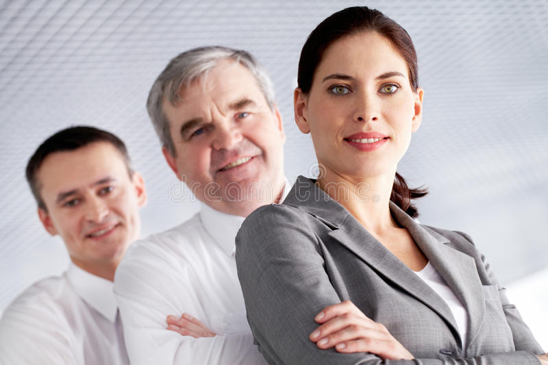 Leader with team. A business team with pretty leader in front looking at camera and smiling royalty free stock image