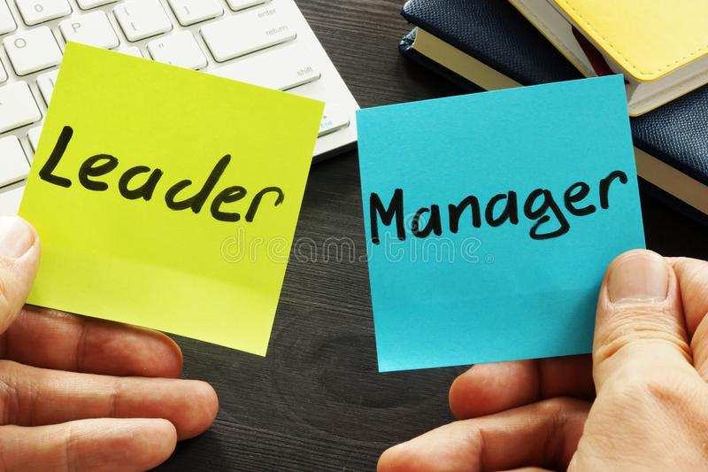 Leader vs manager. Man holding memo sticks. stock photos