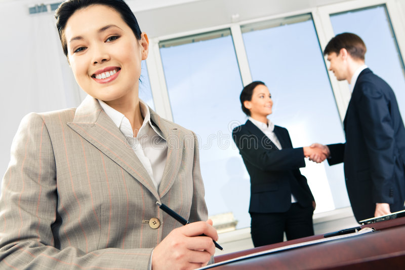 Leader at work. Photo of Asian businesswoman looking at camera on the background of two partners shaking hands stock photo
