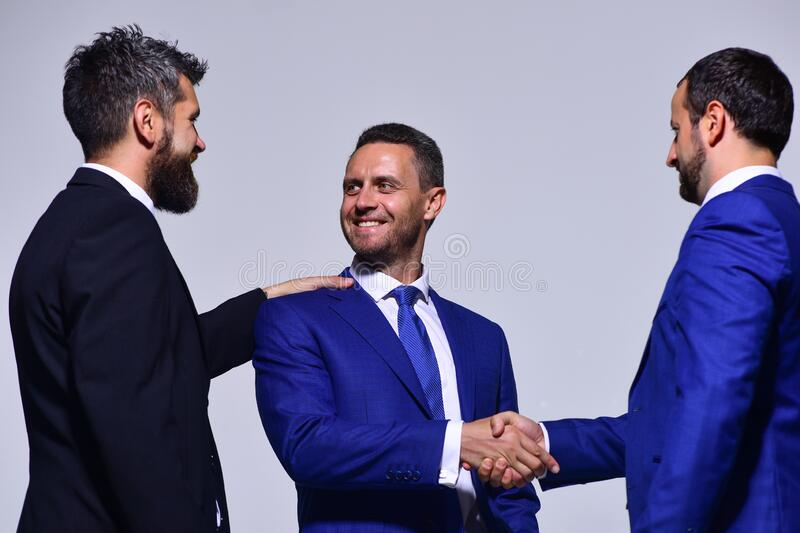 Leaders have business meeting making deal. Businessmen with happy faces. In formal wear on grey background. Coworkers or partners shake hands for cooperation stock photography