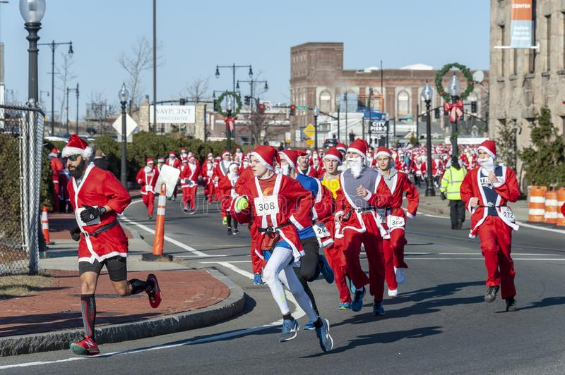 Leaders of the pack. New Bedford, Massachusetts, USA - December 8, 2018: Leading the pack of hundreds of Santas on the move near the start of the Santa Sightings stock photo