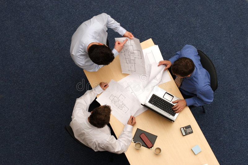 Leadership. Three young executives siting,standing and discussing the contents of a bar chart and what is being shown on a notebook computer.Aerial shot taken stock image
