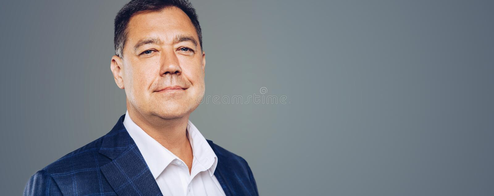 Leadership.Attractive business man looks confident ,studio portrait. Mature and beautiful. Panoramic banner royalty free stock photography