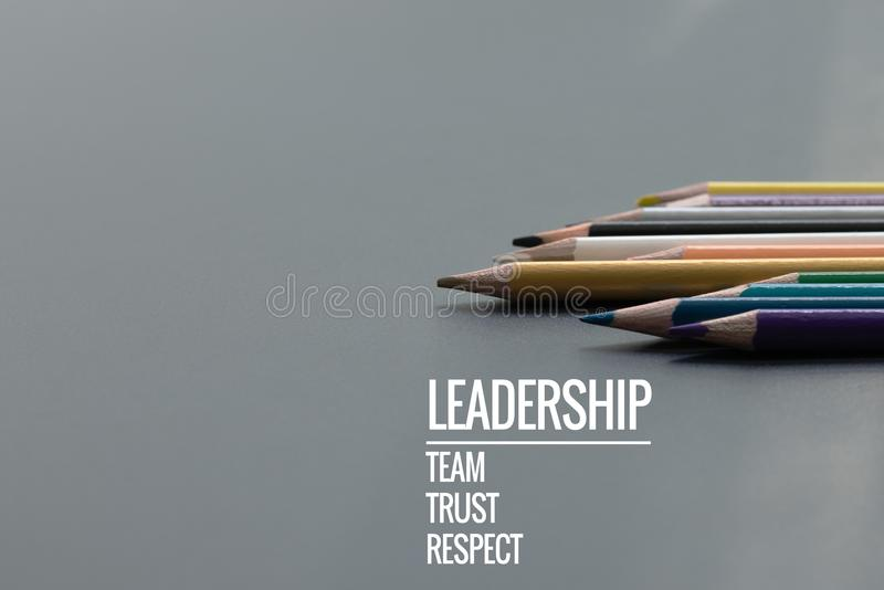 Leadership business concept. Gold color pencil lead other color with word Leadership, team, trust and respect on black background royalty free stock photo