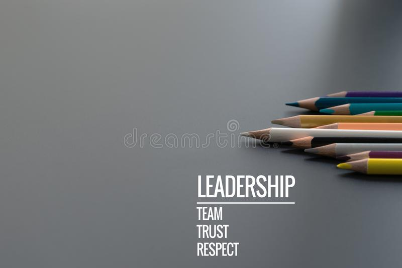 Leadership business concept. Gold color pencil lead other color with word Leadership, team, trust and respect on black background stock photo