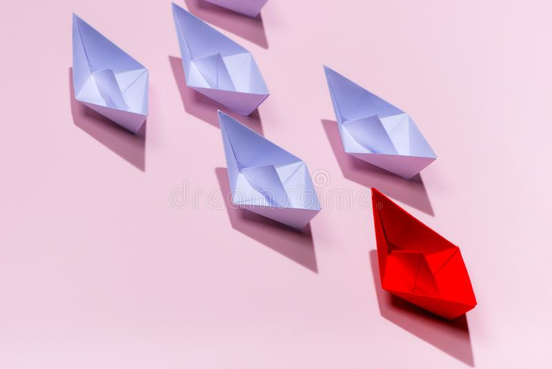 Leadership concept. Red paper ship leading among white.  stock illustration