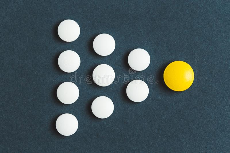 Leadership concept with yellow pill leading among white on blue background royalty free stock image