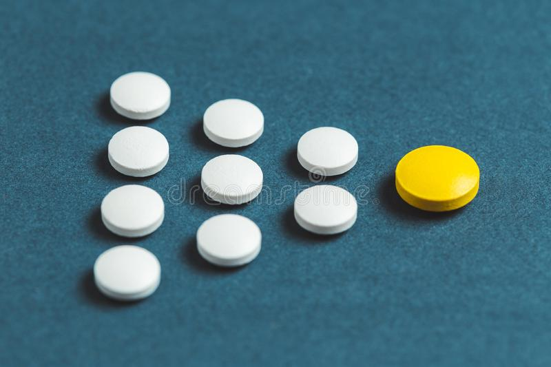 Leadership concept with yellow pill leading among white on blue background royalty free stock photography