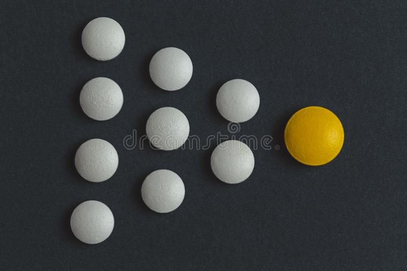 Leadership concept with yellow pill leading among white on blue background stock photos