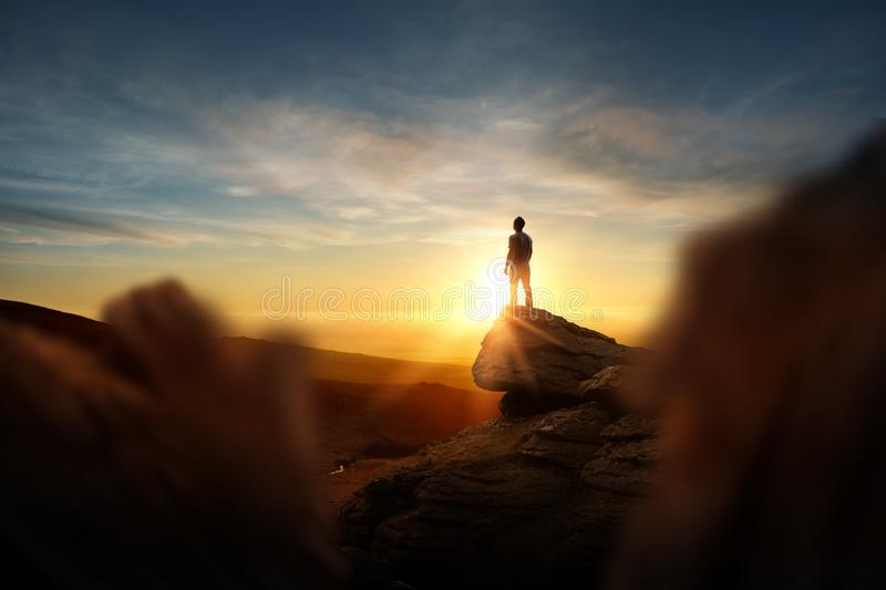Leadership And Goals. A man standning on top of a mountain watching the sun set. Conceptual photo composite stock photo