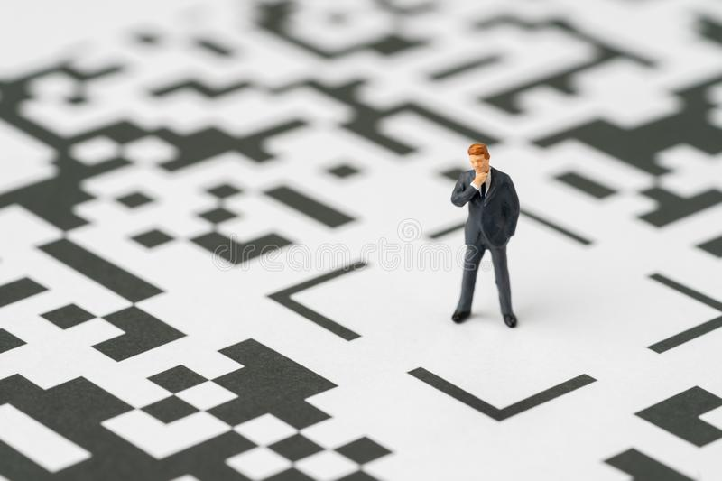 Leadership, solution for business idea concept, miniature figurine businessman standing at the center of confusing QR code. Labyrinth maze thinking to be royalty free stock photography