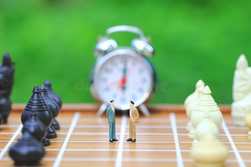Leadership for success game, Miniature businessman standing on chessboard and chess background, Strategy investment and business royalty free stock photo