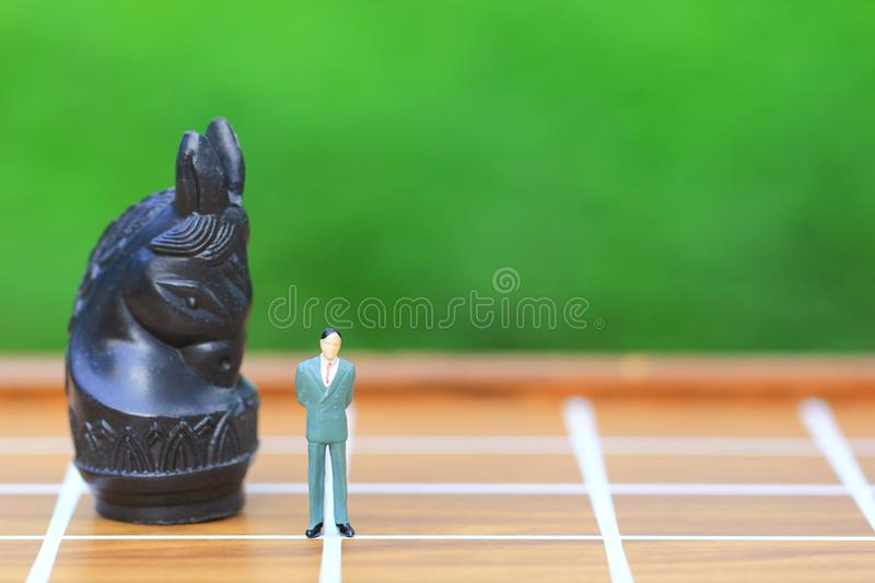 Leadership for success game, Miniature businessman standing on chessboard and chess background, Strategy investment and business. Concept royalty free stock photo