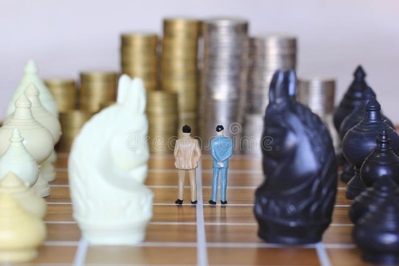 Leadership for success game, Miniature businessman standing on chessboard and chess with stack of coins money background, Strategy. Investment and business stock photos