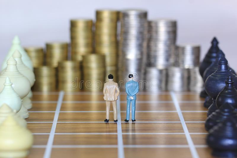 Leadership for success game, Miniature businessman standing on chessboard and chess with stack of coins money background, Strategy. Investment and business stock photo