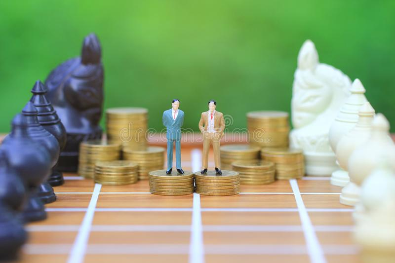 Leadership for success game, Miniature businessman standing on stack of coins money and chess on natural green background,. Strategy investment and business royalty free stock photos