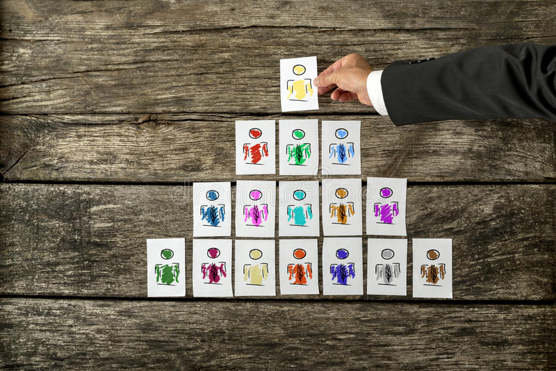 Leadership and team management concept. With a businessman arranging a series of hand-drawn cards depicting people into a pyramid and just about to place the royalty free stock image