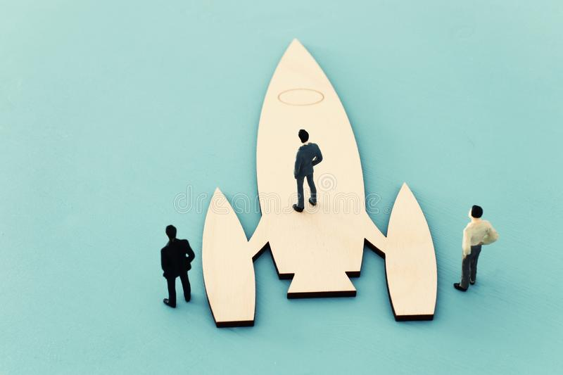 leadership and teamwork concept miniature people and rocket, inspiration and vision. royalty free stock photo