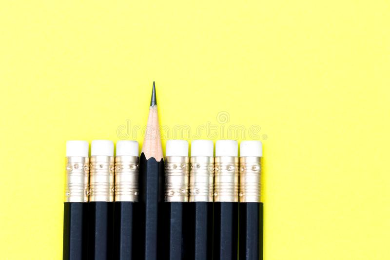 Leadership, think difference concept. One sharpened pencil standing out from the blunt ones over yellow background. leadership, think difference concept stock photo
