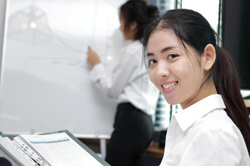 Leadership young Asian business woman looking at camera between listening to presentation in modern office background stock photo