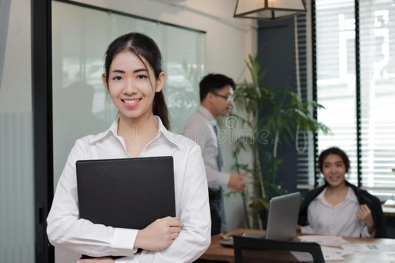 Leadership young Asian business woman standing and smiling with colleage in meeting room background. stock photos