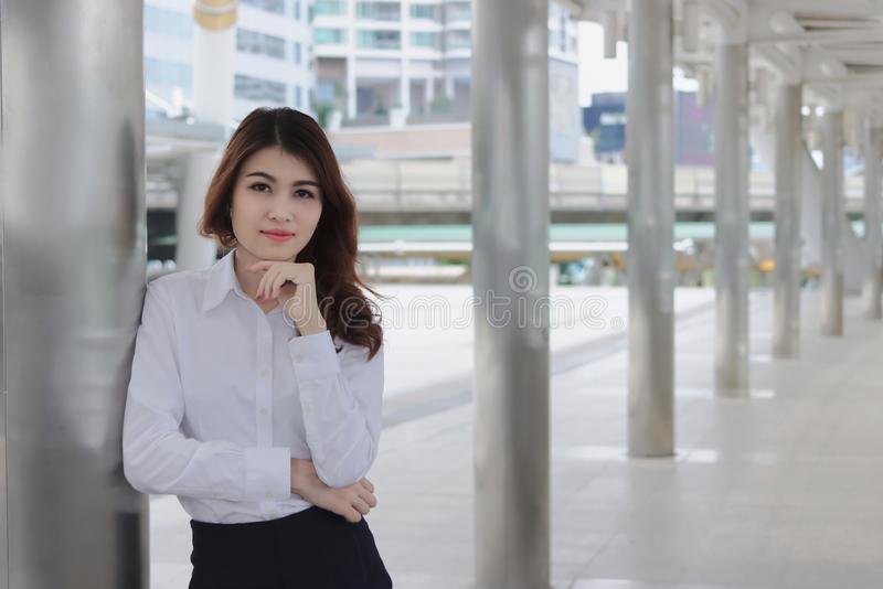 Leadership young Asian businesswoman standing and looking to camera at walkway of outside office royalty free stock photography