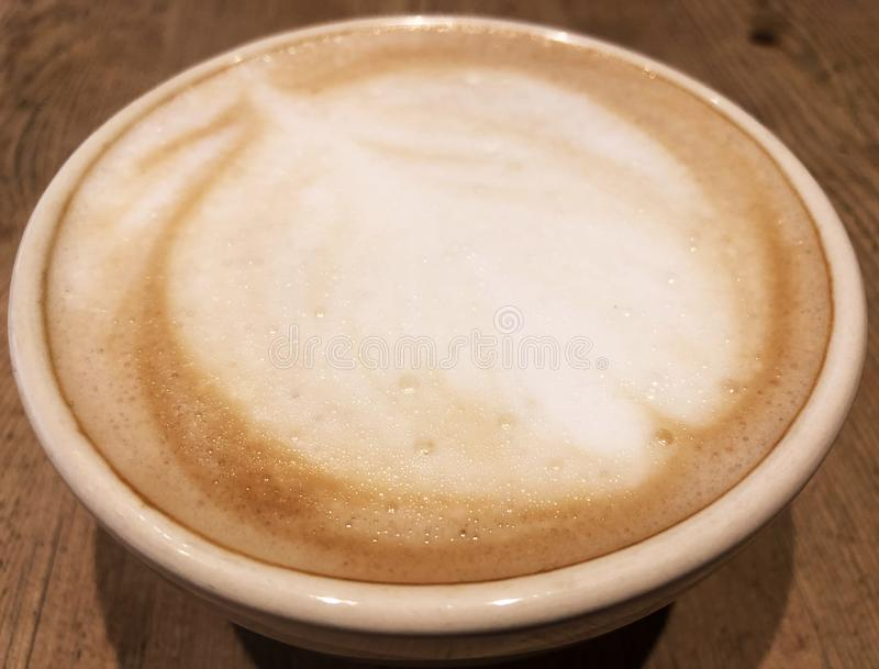 Leaf Foam In Cafe Latte. Artistic leaf created in the white foam of a cafe latte poured in a coffee cup royalty free stock photography