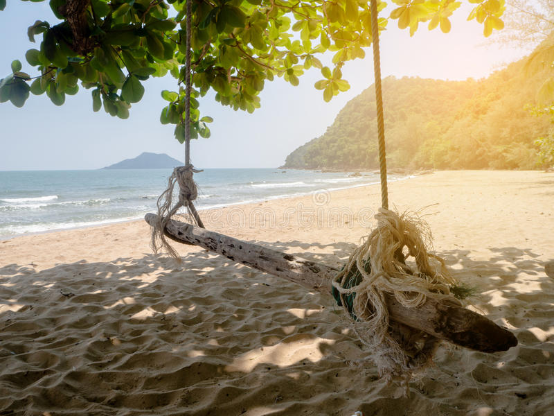 Leaf frame with blank wooden swing on natural blue sea beach ba royalty free stock photo