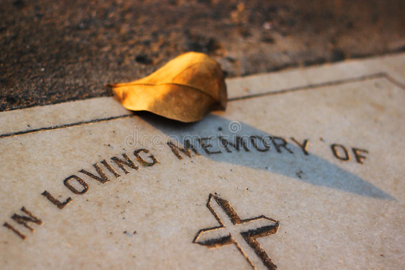 Leaf on a Grave. Grave with the Loving memory message and a leaf stock photography