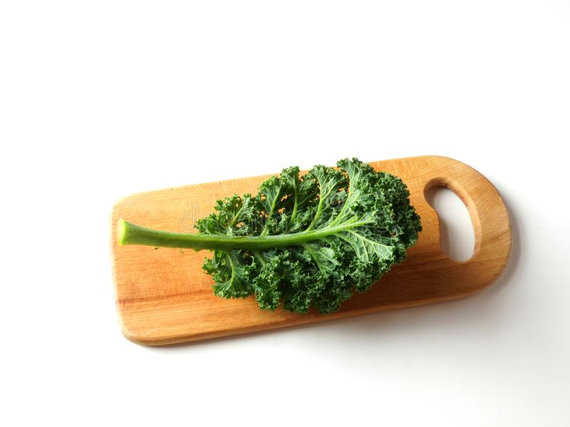 Leaf of kale lies on a wooden cutting board. royalty free stock photos