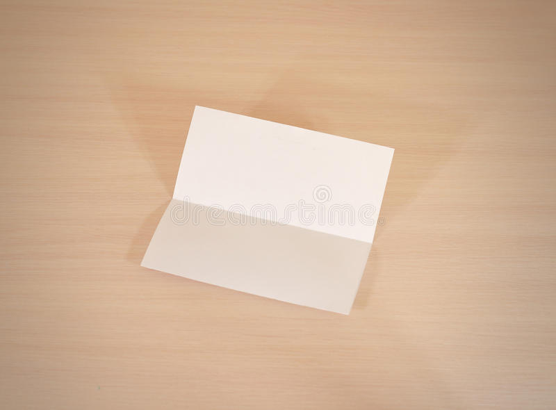 Leaflet blank white paper brochure mockup on a wooden table. Show offset paper. Sheet template. Book in hands. Booklet folding de royalty free stock image