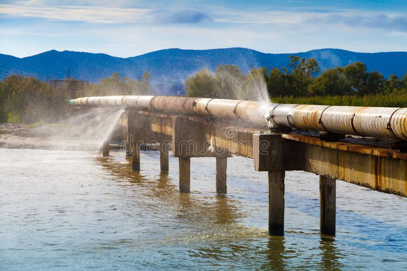 A leaking pipeline in the sun crossing a canal. A leaking pipeline in the sun crossing a canal near the shoreline royalty free stock photo