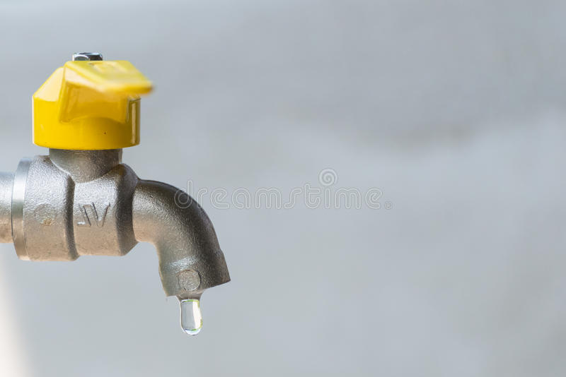 Leaking silver yellow faucet with water drop. Close up, copy space royalty free stock photos