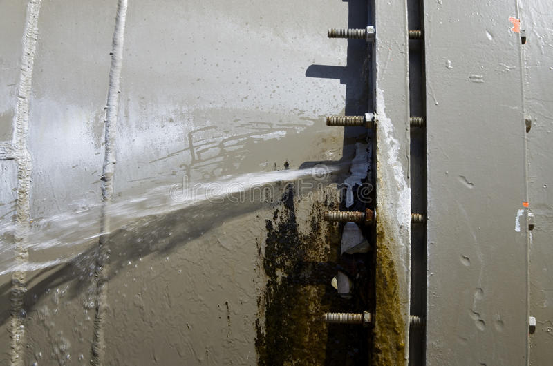 Leaking water pipe. Large aqueduct water pipe leaking from a bolted joint stock image
